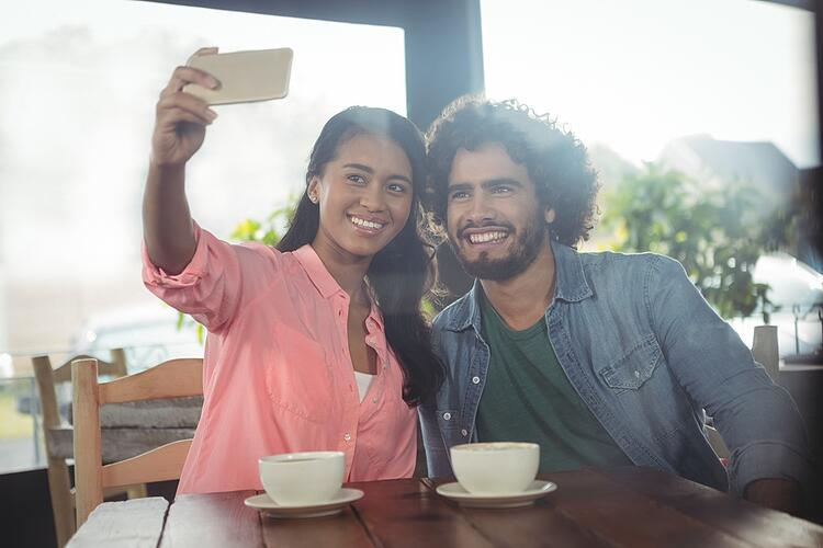 Couple taking selfie from mobile phone in cafeteria