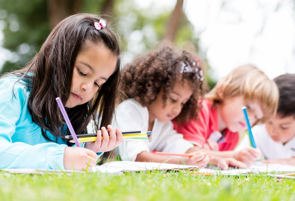 Happy group of children coloring at the park