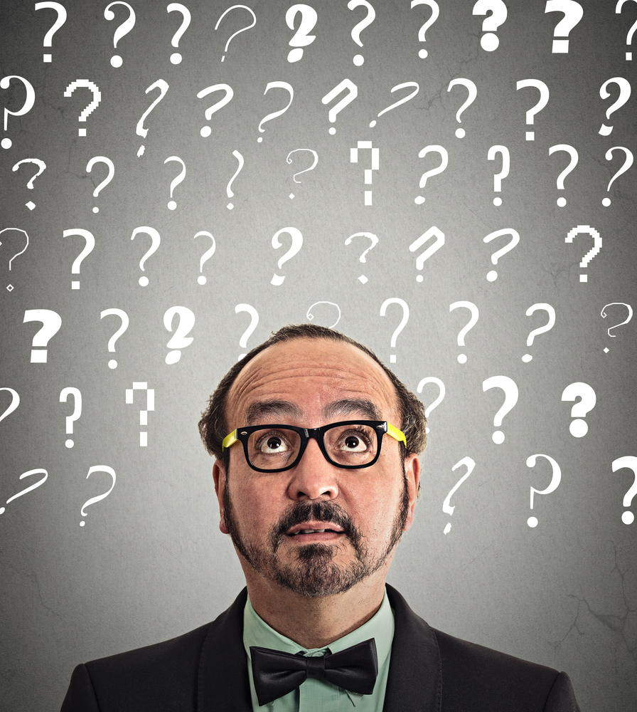 Headshot middle aged man with puzzled face expression and question marks above head looking up isolated grey wall background. Human emotion feeling body language perception problem solution concept